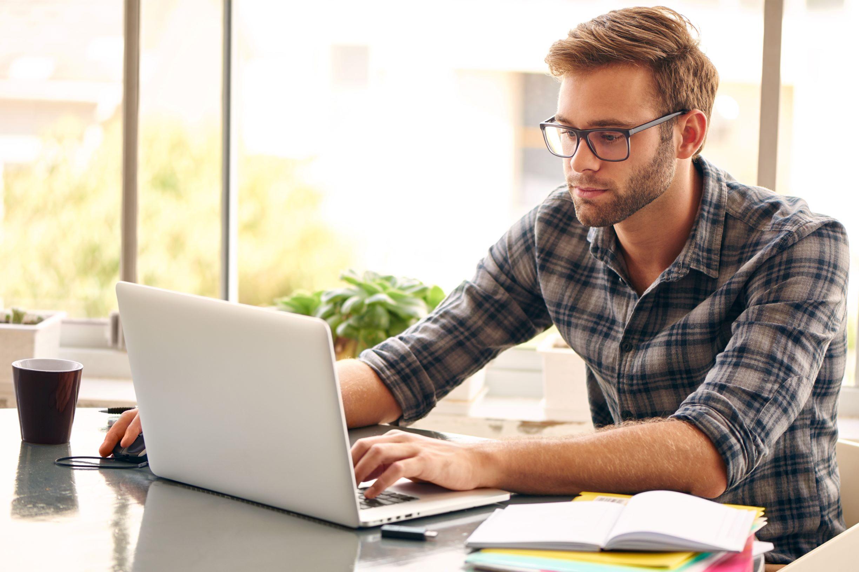 Man sitting at desk working on laptop