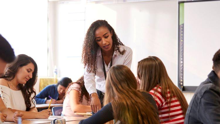 high school teacher helping students during class