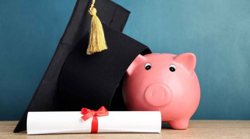 Piggy bank next to diploma and graduation cap